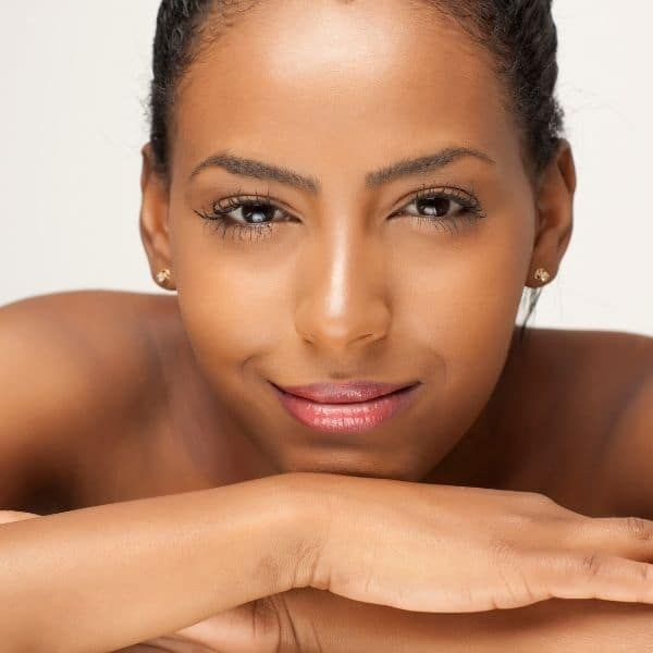 An African american woman smiling as she rests her head on her hands
